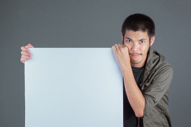 Uomo dai capelli corti che indossa una camicia verde scuro, in piedi con un'etichetta bianca su un grigio. Foto Gratuite