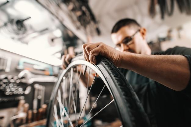 Uomo dedicato caucasico che mette gomma sulla ruota di bicicletta mentre stando nell'officina. Foto Premium