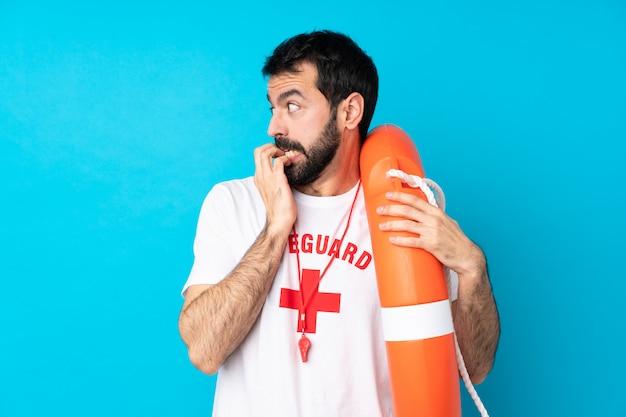 Uomo del bagnino sopra la parete blu isolata nervosa e spaventata mettendo le mani alla bocca Foto Premium