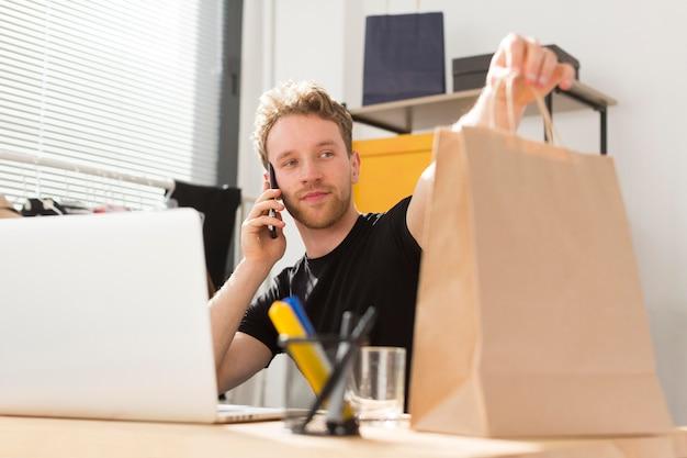 Uomo del colpo medio che tiene sacco di carta Foto Gratuite