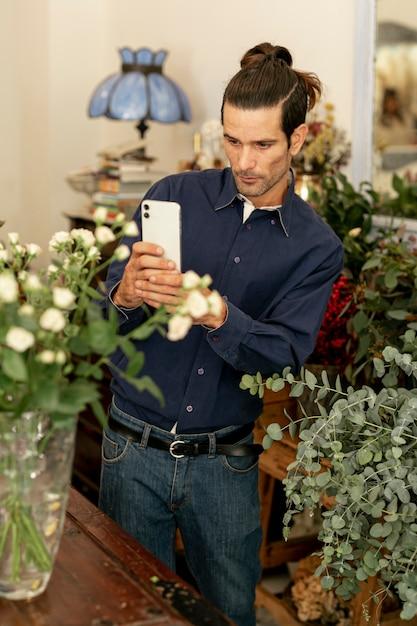 Uomo del giardiniere con capelli lunghi che prende una foto Foto Gratuite