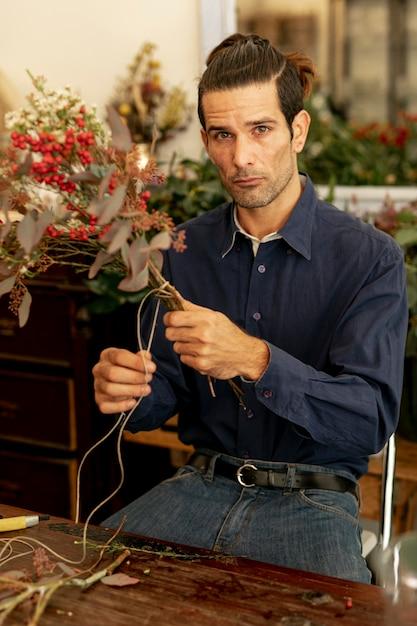 Uomo del giardiniere con capelli lunghi che taglia una corda Foto Gratuite