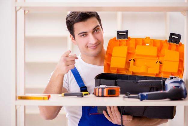 Uomo del lavoratore che ripara lo scaffale per libri di montaggio Foto Premium