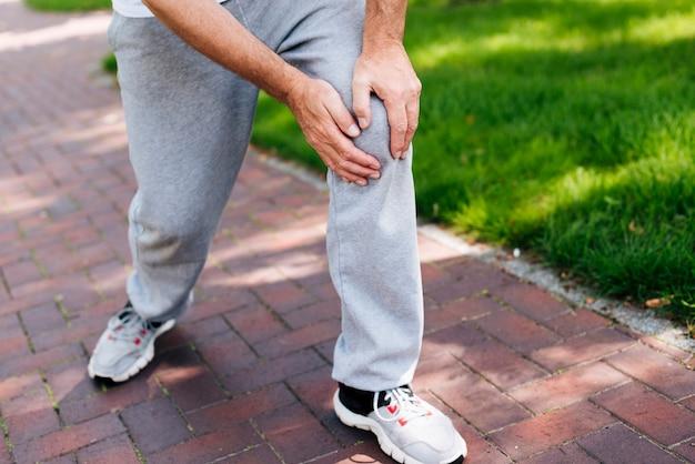 Uomo del primo piano che avverte dolore al ginocchio Foto Gratuite