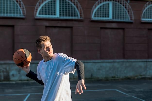 Uomo del tiro medio che getta una pallacanestro Foto Gratuite