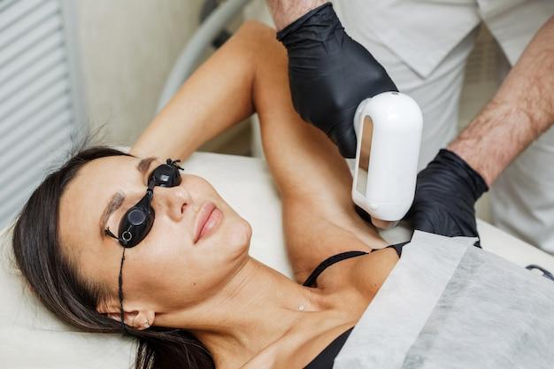 Uomo dell'estetista che applica depilazione o epilazione del laser nella zona dell'ascella per la donna nel salone della stazione termale Foto Premium
