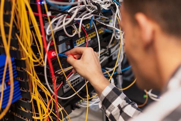 Uomo dell'ingegnere che collega la fibra ottica allo switch ethernet Foto Gratuite