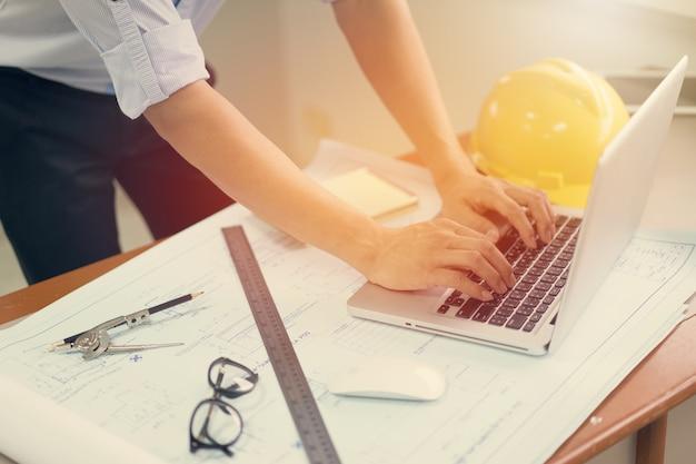 Uomo dell'ingegnere che lavora con il computer portatile e cianografie che schizzano un progetto di costruzione Foto Premium