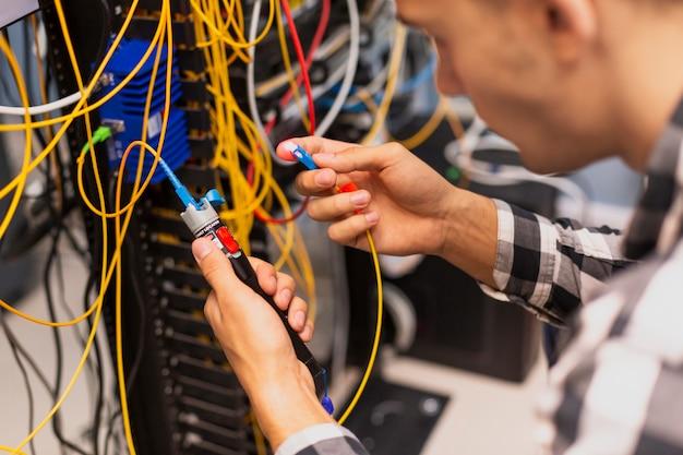Uomo dell'ingegnere che verifica la fibra ottica Foto Gratuite