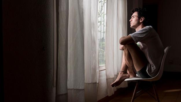 Uomo della foto a figura intera che si siede sulla sedia all'interno Foto Gratuite