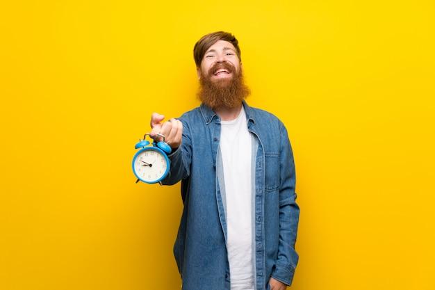 Uomo della testarossa con la barba lunga sopra la parete gialla isolata che tiene sveglia d'annata Foto Premium