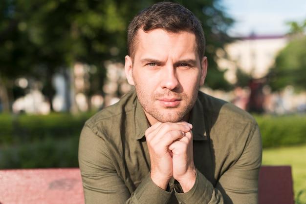 Uomo delle stoppie che si siede sulla panchina che guarda l'obbiettivo nel parco Foto Gratuite