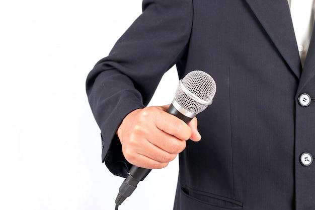Uomo di affari che giudica un microfono isolato su priorità bassa bianca Foto Premium