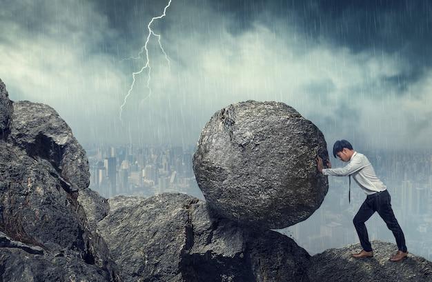 Uomo di affari che spinge grande pietra fino alla collina, compiti pesanti di affari e concetto di problemi. Foto Premium
