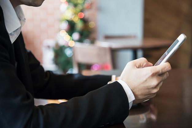 Uomo di affari che utilizza telefono cellulare mentre bevendo caffè in caffetteria Foto Gratuite