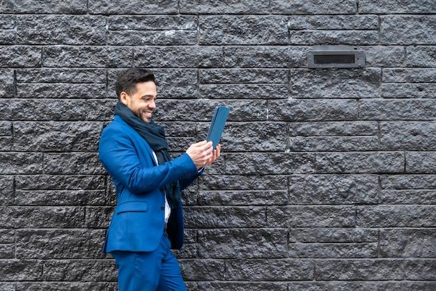 Uomo di affari sul vestito blu che cattura maschera con il ridurre in pani. Foto Premium