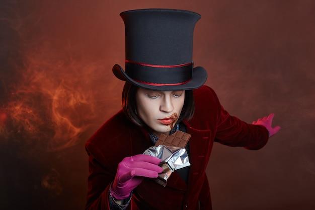 Uomo di circo favoloso in un cappello e un abito rosso in posa nel fumo su un buio Foto Premium