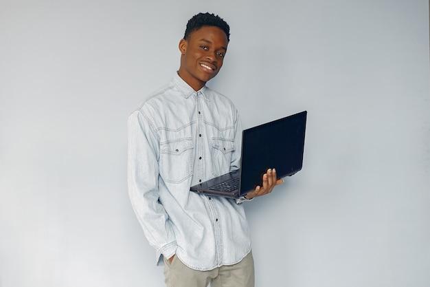 Uomo di colore bello che sta su una parete blu Foto Gratuite