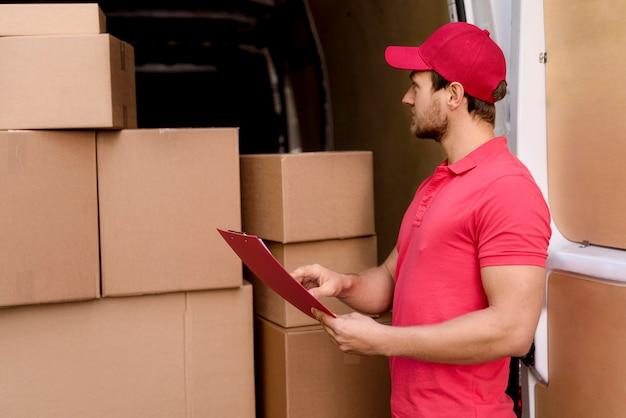 Uomo di consegna che controlla la lista dei pacchetti Foto Gratuite