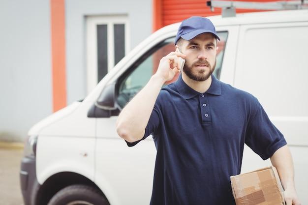 Uomo di consegna che fa una telefonata mentre si tiene un pacchetto Foto Premium