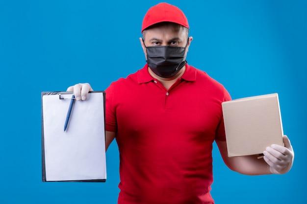 Uomo di consegna che indossa uniforme rossa e cappuccio in maschera protettiva facciale tenendo la scatola di cartone e appunti con spazi vuoti con grave accigliato viso su backg blu Foto Gratuite