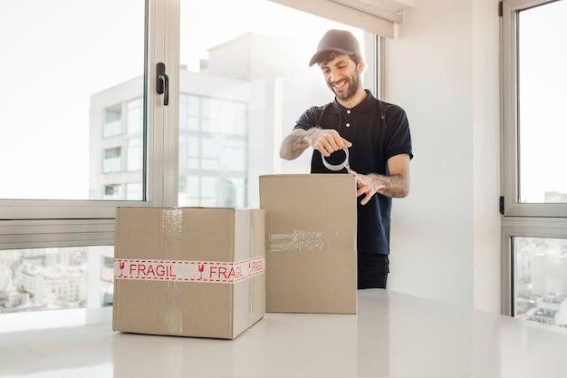 Uomo di consegna che lega su scatole di cartone Foto Gratuite