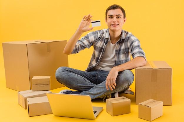 Uomo di consegna che mostra la carta di credito Foto Gratuite