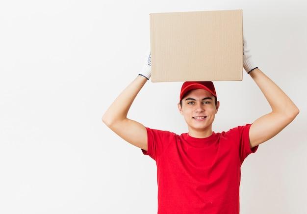 Uomo di consegna che tiene il pacchetto sopra la testa Foto Gratuite