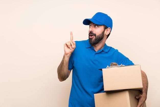 Uomo di consegna con la barba sopra il muro isolato con l'intenzione di realizzare la soluzione mentre si solleva un dito Foto Premium
