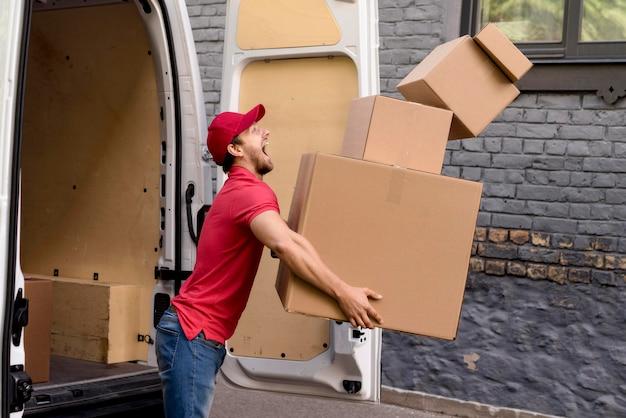 Uomo di consegna con pila di pacchi Foto Gratuite