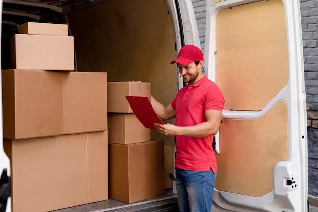 Uomo di consegna dell'angolo alto che controlla la lista dei pacchetti Foto Gratuite