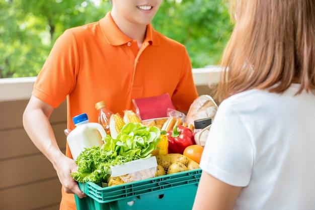 Uomo di consegna della drogheria che consegna alimento ad una donna a casa Foto Premium