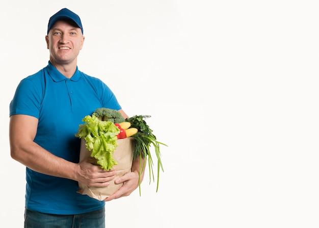 Uomo di consegna di smiley che posa con la borsa di drogheria Foto Gratuite