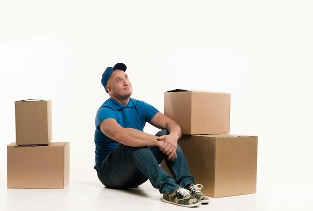 Uomo di consegna di smiley che posa con le scatole di cartone Foto Gratuite