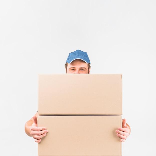 Uomo di consegna in piedi con due grandi scatole Foto Gratuite