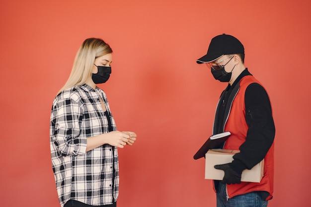 Uomo di consegna in una maschera medica con donna Foto Gratuite