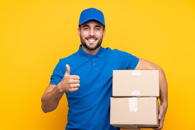 Uomo di consegna su giallo isolato con il pollice in alto perché è successo qualcosa di buono Foto Premium
