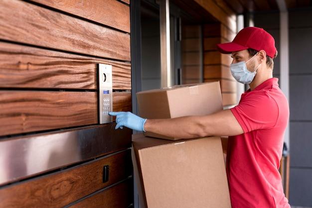 Uomo di consegna vista laterale che suona alla porta Foto Gratuite