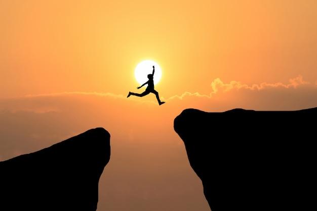Uomo di coraggio salta attraverso il divario tra collina, idea di business concept Foto Gratuite