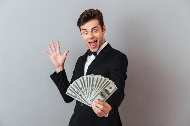 Uomo di grido emozionante in vestito ufficiale che tiene soldi. Foto Gratuite