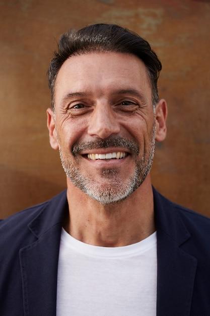 Uomo di mezza età che indossa una giacca che ride felice Foto Gratuite