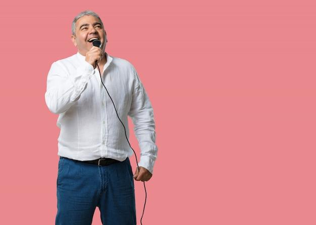 Uomo di mezza età felice e motivato, cantando una canzone con un microfono Foto Premium
