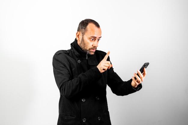 Uomo di mezza età in cappotto con gesto di stupore mentre parla sul suo telefono cellulare, isolato su bianco. Foto Premium
