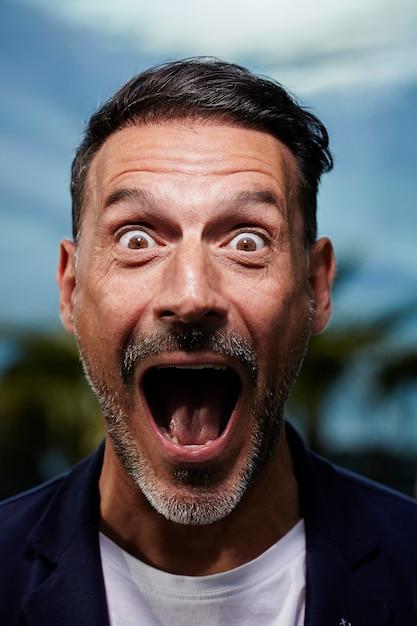 Uomo di mezza età sorpreso con un cielo blu Foto Gratuite