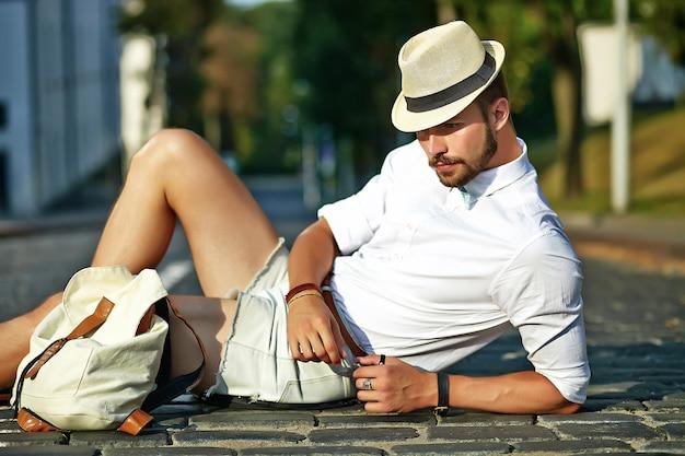 Uomo di modello bello hipster in abiti estivi alla moda che si siede in cappello con la borsa Foto Gratuite