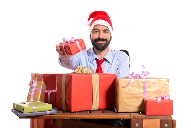 Uomo di natale nel suo ufficio con diversi regali for Regali per ufficio