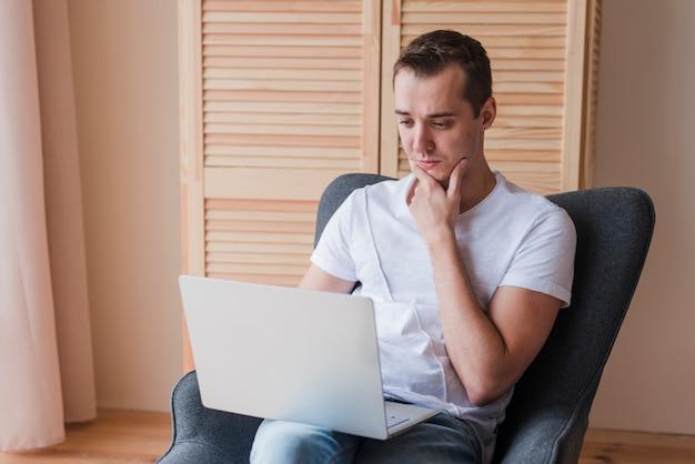 Uomo di pensiero che si siede sulla sedia e che utilizza computer portatile nella sala Foto Gratuite