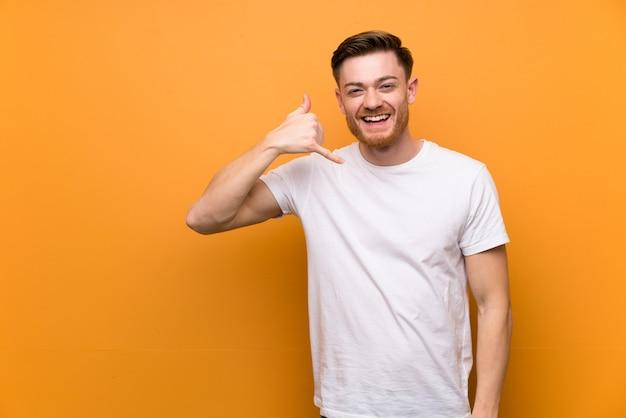 Uomo di redhead sulla parete marrone facendo il gesto del telefono, richiamami segno Foto Premium