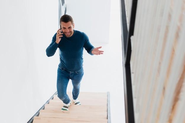 Uomo di smiley che sale le scale e che parla al telefono Foto Gratuite