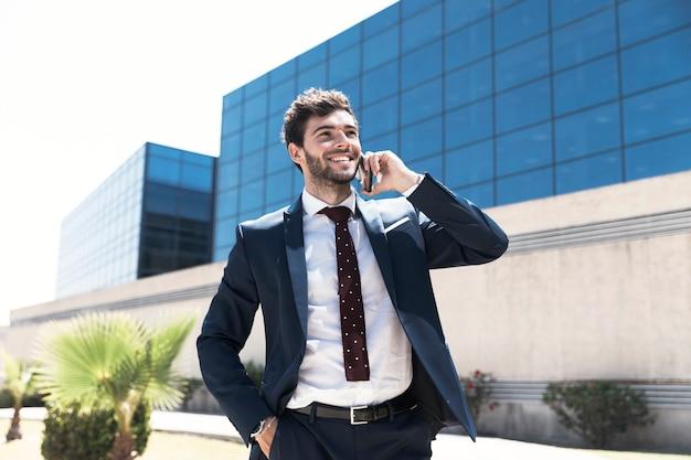Uomo di smiley del colpo medio che parla sul telefono Foto Gratuite